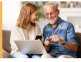 Uśmiechnięci młoda kobieta i starszy mężczyzna z brodą siedzą na kanapie. Kobieta w ręku trzyma telefon, a na kolanach ma położny laptop