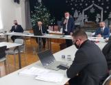 Grupa osób siedzących przy stołach. Jeden mężczyzna stoi i trzyma mikrofon w ręce. W tle widoczna choinka i dekoracja świąteczna.