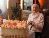 Starsza kobieta siedzi na krześle. Przed nią na stole leży tort ze świeczkami 100