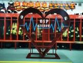 Duże, czerwone, metalowe serce (pojemnik) z napisem OSP Grębów. W tle szafki z ubraniami, butami strażaków