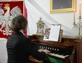 Mężczyzna gra na fortepianie, na który stoi kartka z nutami oraz świecznik. Po prawej stronie widoczny godło Polski (biały orzeł na czerwonym tle)