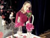 Młoda dziewczyna w bordowej bluzce siedzi przy stole w ręce trzyma różę. Na stole stoi świecznik.