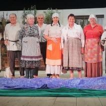 Na scenie stoją w rzędzie mężczyźni i kobiety w chustach na głowie.