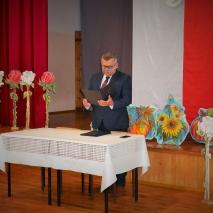Mężczyzna stoi przy stoliku nakrytym białym obrusem. W ręku trzyma ciemną teczkę. Z tyłu znajdują się dekoracje w formie kwiatów. Po prawej stronie tło tworzy biało czerwony materiał.