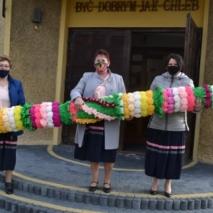 Trzy kobiety w maseczkach trzymają dużą palme