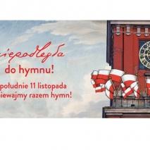 Po prawej część budynku z zegarem, na tarasie wywieszone wiele flag biało czerwonych. Po lewej czerwony napis: niepodelgła do hymnu, w południe 11 listopada zaśpiewajmy razem hymn.