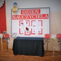 Pozioma tablica stojąca na stole przykrytym ciemnym materiałem z napisem dzień nauczyciela . W lewym roku ozdobna sowa w  niebieskiej czapce. Na podłodze stoją dekoracyjne białe i czerwone kwiaty.